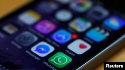 FILE - WhatsApp and Facebook messenger are among app icons seen on an iPhone.
