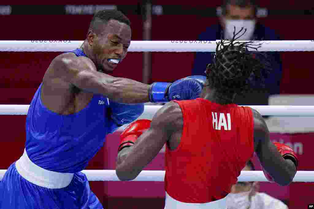 Haiti's Darrelle Valsaint Jr., right, takes a punch from David Tshama Mwenekabwe, of the Democratic Republic of the Congo, during their men's middleweight 75-kg boxing match at the 2020 Summer Olympics, Thursday, July 29, 2021, in Tokyo, Japan. (AP Photo/Frank Franklin II)
