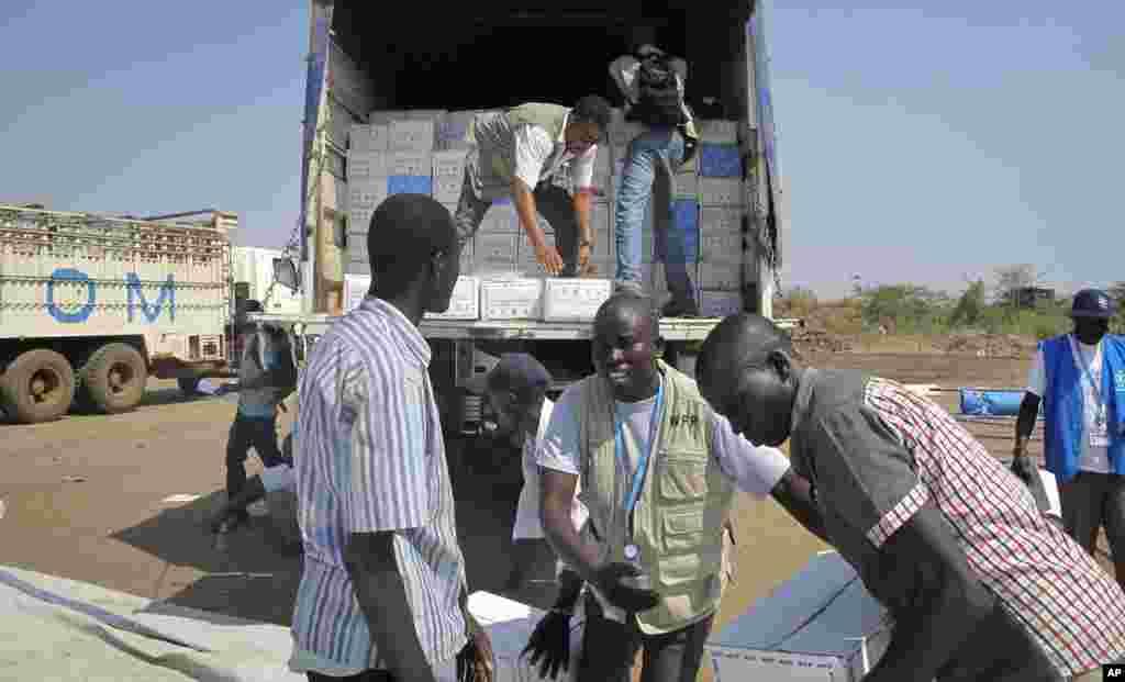 wafanyakazi wa WFP wakipakua msaada wa vyakula kutoka eneo la umoja wa mataifa ambako watu wengi waliokoseshwa makazi wamehifadhiwa.