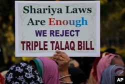 """In this Jan. 7, 2018 file photo, an Indian Muslim woman holds a placard during a protest against a new draft law aimed at banning """"Triple Talaq,"""" a Muslim practice of instant divorce, in Ahmadabad, India. India's government on Wednesday, Sept. 19, approve"""