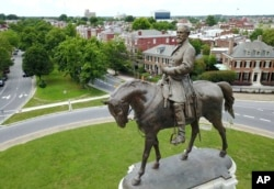 FILE - The statue of Confederate Gen. Robert E. Lee stands in the middle of a traffic circle on Monument Avenue in Richmond, Virginia.