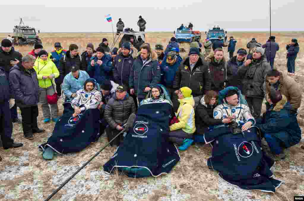 Russian cosmonauts Mikhail Kornienko, left, Sergey Volkov of Roscosmos, center, and Expedition 46 Commander Scott Kelly of NASA, rest in chairs outside of the Soyuz TMA-18M spacecraft just minutes after they landed in a remote area near the town of Zhezkazgan, Kazakhstan.