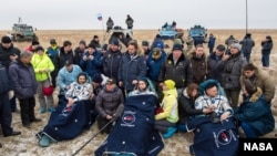 FILE - Russian cosmonauts Mikhail Kornienko, left, Sergey Volkov of Roscosmos, center, and Expedition 46 Commander Scott Kelly of NASA, rest in chairs outside of the Soyuz TMA-18M spacecraft just minutes after they landed in a remote area near the town of Zhezka