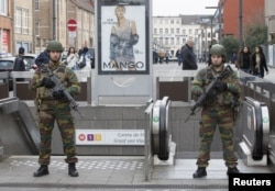 Belgian soldiers keep guard outside a metro station during tensions between police and residents, in the Brussels neighborhood of Molenbeek, April 2, 2016.
