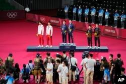 東京奧運會羽毛球男雙頒獎台上,台灣選手李洋及王齊麟獲金牌,中國選手李俊慧與劉雨辰獲銀牌,馬來西亞選手獲銅牌。(2021年7月31日)