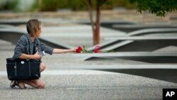 A woman reaches out to touch flowers placed on one of the benches of the Pentagon Memorial at the Pentagon, outside Washington, Sept. 11, 2014.