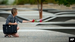 Seorang perempuan menyentuh bunga di bangku di Memorial Pentagon. (Foto: Dok)