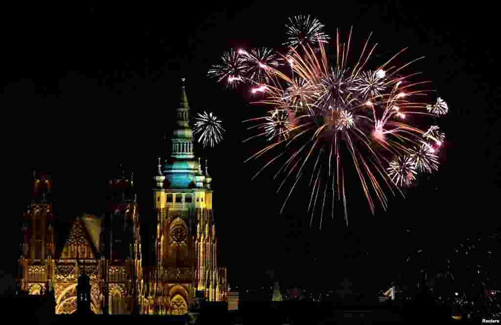Fireworks explode over the towers of the St. Vitus Cathedral at Prague Castle, Czech Republic, to mark the first day of the New Year, Jan. 1, 2018.