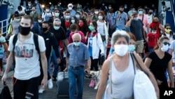 Arhiva - Putnici sa medicinskim maskama iskrcaravju se sa trajktea u luci Pirej, u blizini Atine, Grčka, 20. avgusta 2020.