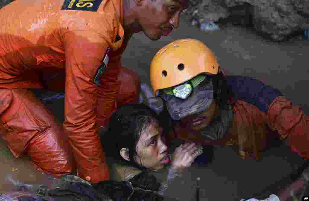 Rescuers evacuate a survivor following earthquakes and tsunami in Palu, Central Sulawesi, Indonesia. Rescuers were scrambling to try to find trapped victims in collapsed buildings where voices could be heard screaming for help after a massive earthquake in Indonesia spawned a deadly tsunami two days ago.