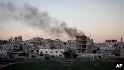 Asap hitam mengepul menyusul hantaman mortir di wilayah permukiman warga saat terjadinya pertempuran antara pasukan pemerintah dan pemberontak pecah di wilayah Maaret al-Numan , provinsi Idlib, Suriah, 9 Oktober 2013 (Foto: dok).