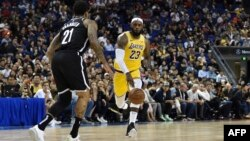 LeBron James of the Los Angeles Lakers (R) drives the ball in front of Wilson Chandler of the Brooklyn Nets (L) during the National Basketball Association (NBA) pre-season match between the LA Lakers and Brooklyn Nets at the Mercedes Benz Arena in Shanghai.