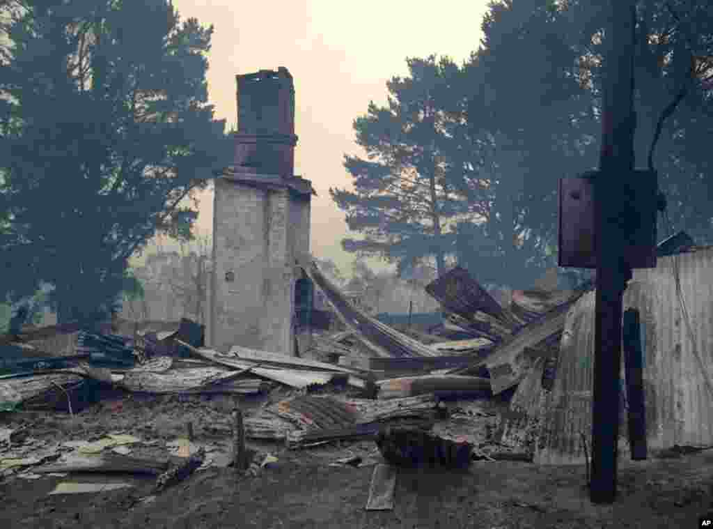 In this photo provided by the New South Wales Rural Fire Service, the remains of a structure are in a crumpled pile after a wildfire destroyed the building, at an unknown location in Australia, Oct. 17, 2013.