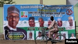 FILE PHOTO: A cyclist rides past a campaign poster for President Muhammadu Buhari days before the presidential election in Kano, Nigeria, Feb. 17, 2019.