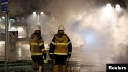 Firefighters keep an eye on several cars that were set on fire during a riot, according to local media, in Rinkeby suburb, outside Stockholm, Sweden, Feb. 21, 2017.