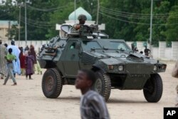 FILE - Nigerian soldiers ride on the armored vehicle in Maiduguri, Nigeria, Aug. 8, 2013. Nigeria is among the few African countries that have increased their military budgets in recent years.
