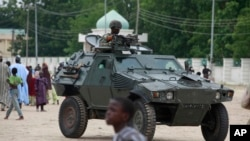 (File) Nigerian soldiers ride on the armored tank in Maiduguri, Nigeria.