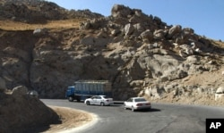 Vehicles take a sharp turn on a troubled highway near Pol-I-Kumari, Afghanistan, along the one time Silk Road route. Growing Taliban influence in northern Afghanistan is threatening the new military supply line painstakingly negotiated by the U.S.,
