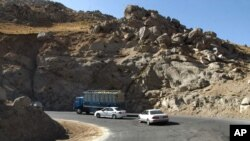 Vehicles take a sharp turn on a troubled highway near Pol-I-Kumari, Afghanistan, along the one time Silk Road route.