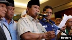 Kandidat presiden Indonesia, Prabowo Subianto memberikan pidato untuk menyatakan kemenangan pemilu saat pasangannya Sandiaga Uno berdiri di sebelahnya di Jakarta, Indonesia, 18 April 2019.