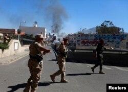 手持機槍的也門軍人在國防部爆炸現場街道巡邏。