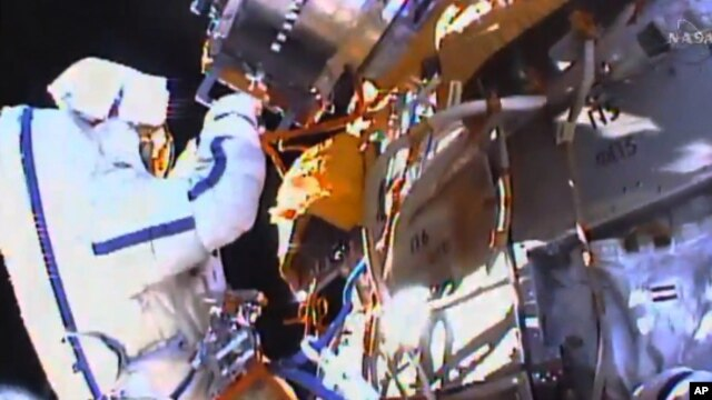 This photo taken from video provided by NASA shows Russian cosmonauts Yuri Malenchenko and Sergey Volkov install fresh experiments outside the International Space Station on Feb. 3, 2016.