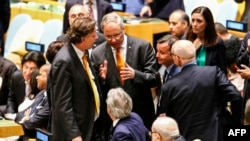 Duta Besar Belanda untuk PBB Karel van Oosterom (tengah) berbicara dengan Menteri Luar Negeri Italia Paolo Gentiloni (duduk, tengah), disaksikan Menteri Luar Negeri Belanda Bert Koenders (kiri) dan Duta Besar Italia untuk PBB Sebastiano Cardi (kanan) dalam sidang Dewan Keamanan PBB di New York (28/6). (AFP/Kena Betancur)