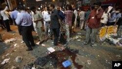 21일 인도 하이데라바드의 번화가에서 일어난 폭탄테러. 폭탄테러의 잔해 주위에 사람들이 모여있다.