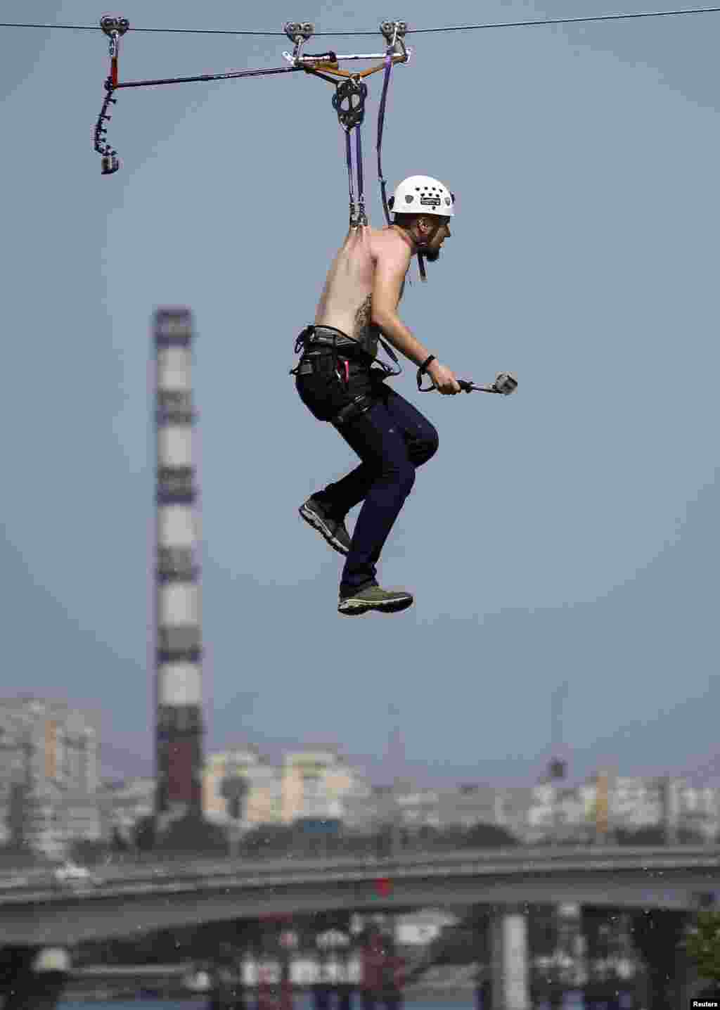 Pavlo Klets, 24, rides a Tyrolean traverse over the Dnipro River, suspended by a cable wire with metal clamps pierced directly into the skin of his back to set a national record for the longest distance travelled on a Tyrolean traverse.
