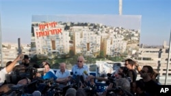 FILE - Israeli Minister of Housing and Construction Uri Ariel, center, speaks to journalists during ceremony marking resumption of construction in east Jerusalem.