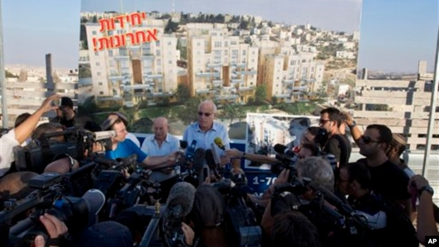 Israeli Minister of Housing and Construction Uri Ariel, center, speaks to journalists during ceremony marking resumption of construction in east Jerusalem, Aug. 11, 2013.