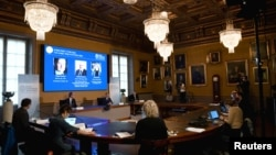 David Haviland, member of the Nobel Committee for Physics, Goran K. Hansson, Secretary General of the Royal Swedish Academy of Sciences and Ulf Danielsson, member of the Royal Swedish Academy of Sciences, announce the winners of the 2020 Nobel Prize in Physics, seen on screen.