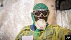 Một nhân viên y tế kiểm tra Ebola cho bệnh nhân bên trong một căn lều khám bệnh ở Bệnh viện Chính phủ Kenema ở Sierra Leone.