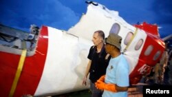 Investigators walk near a section of the tail of AirAsia Flight QZ8501 passenger plane in Kumai Port, near Pangkalan Bun, Central Kalimantan, Jan. 11, 2015.