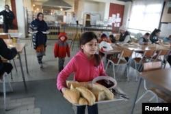 Sonya, 8, daughter of Afghan refugee Najibullah, carries food at the camp for refugees and migrants in the Belgrade suburb of Krnjaca, Serbia, Jan. 16, 2018.
