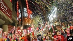 Revelers wave banners and signs during the New Year's Eve celebrations in Hong Kong's Times Square, Jan 1, 2011
