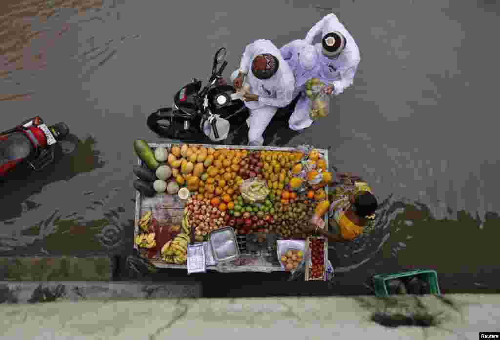 Người mua trái cây từ người bán rong trên đường phố ngập nước sau trận mưa lớn ở thành phố Ahmedabad phía tây Ấn Độ.