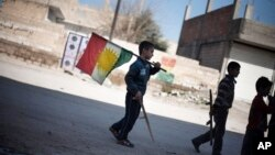 FILE - A boy carries a Kurdish flag on a street in Ras al-Ayn, Syria, Feb. 26, 2013. Taking advantage of the chaos of the civil war, Syria's Kurdish minority has carved out a once unthinkable independence in their areas, even going public with their language and culture.