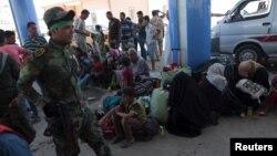 Šiitski borac prolazi pored sunitskih muslimana koji su pobegli od nasilja u Ramadiju