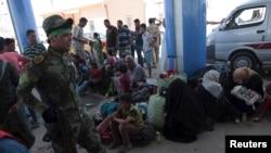 19일 이라크 시아파 민명대가 라마디 시의 수니파 난민들 곁을 지나고 있다.
