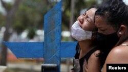 Kelvia, 16 ans, et sa tante, en pleurs lors de l'enterrement de sa mère Andrea dos Reis Brasao, décédée à 39 ans des suites de la maladie à coronavirus, Manaus, Brésil, 17 janvier 2021. (Reuters/Bruno Kelly)