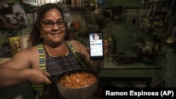 """Contributor Yuliet Colon poses for a photo holding a pot of her creation, """"Cuban-style pisto manchego,"""" and her phone that displays the Facebook page, """"Recipes from the Heart,"""" in her home in Havana, Cuba, Friday, April 2, 2021.(AP Photo/Ramon Espinosa)"""