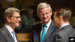 German Foreign Minister Guido Westerwelle (left) talks with Swedish Foreign Minister Carl Bildt (center) and Poland's Foreign Minister Radoslaw Sikorski during a European foreign ministers meeting in Luxembourg, June 24, 2013.
