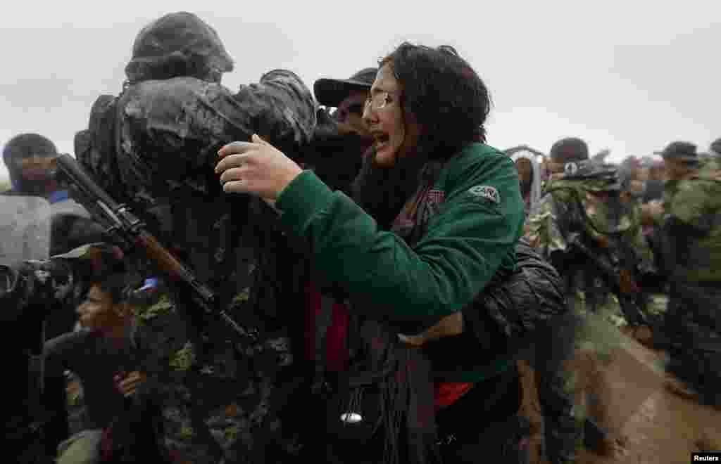 Uma refugiada síria e o seu irmãi tentam escapar a um polícia macedónio, na tentativa de atravessarem a fronteira da Grécia para a Macedónia, junto à vila grega de Idomeni. Set. 10, 2015