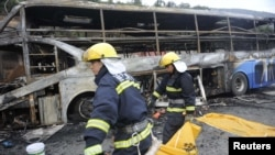 Firefighters carry a victim in a body bag as they work at the accident site after a collision between a bus and a methanol-loaded tanker occurred in Yan'an, Shaanxi province, August 26, 2012.