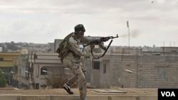 Pasukan NTC Libya yang bersenjata mesin menembaki kubu pendukung Gaddafi di kota Sirte (13/10).