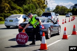 FILE - A Queensland police officer moves a stop sign at a vehicle checkpoint on the Pacific Highway on the Queensland - New South Wales border, in Brisbane, Apr. 5, 2020.