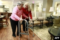 Alexis McKenzie, right, executive director of an Alzheimer's assisted-living home in Washington, walks with resident Catherine Peake in February