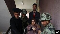 警察和武裝士兵星期二幫助這名投票後的殘疾婦女下樓梯