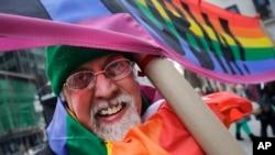"""L'artiste Gilbert Baker, créateur du drapeau arc-en-ciel, porte une pancarte """" Boycottons l'homophobie"""" lors de la parade pour la Saint Patrick à New York, le 17 mars 2014"""
